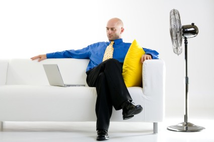 Businessman relaxing on a white couch with a laptop computer beside him to his right. A large standing fan is to his left, pointed in his direction. Isolated on a white background.