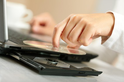 woman's hand placing optical disk on optical drive on laptop
