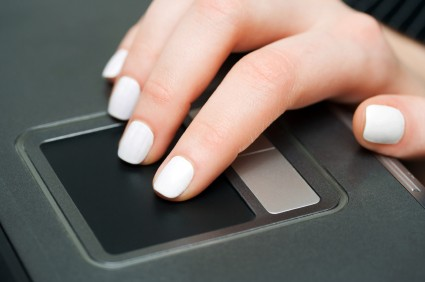 Close-up of female hand working on a laptop touchpad